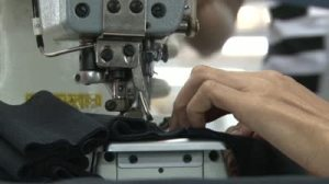stock-footage-close-up-side-view-of-industrial-sewing-machine-in-garment-factory-with-worker-s-hand-feeding-black